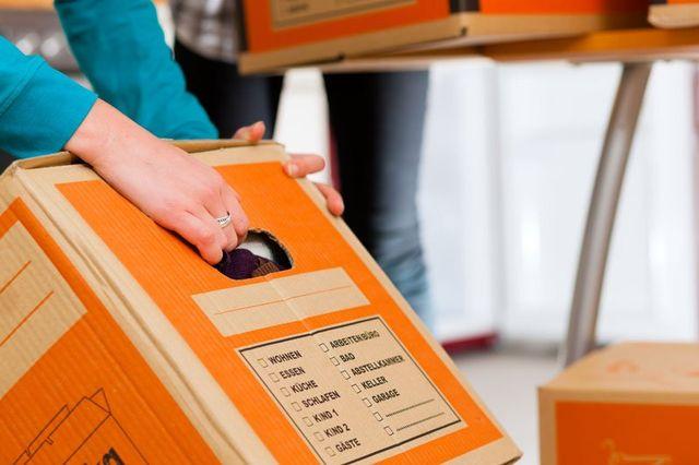 le mani di una donna che indossa un golf azzurro mentre afferrano uno scatolone arancione dalla maniglia