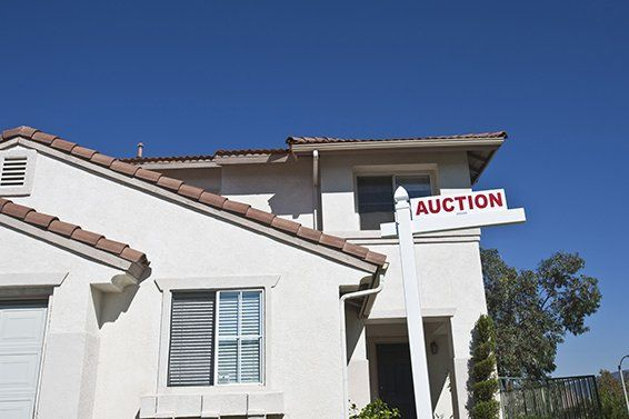 House with auction Sign against blue sky