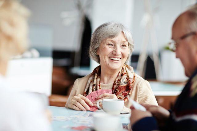 Anziani felici giocano a carte in una casa di riposo