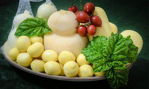 un piatto con scamorzine una mozzarella con basilico, dei pomodorini e altri formaggi