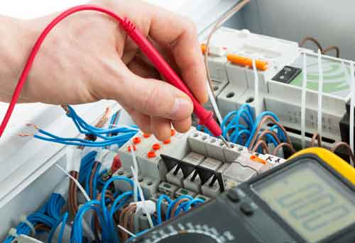 Hand of an electrician with multimeter probe at an electrical switchgear cabinet