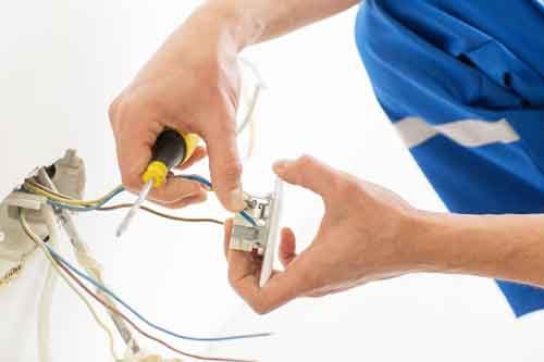 close up of electrician hands with screwdriver fixing socket