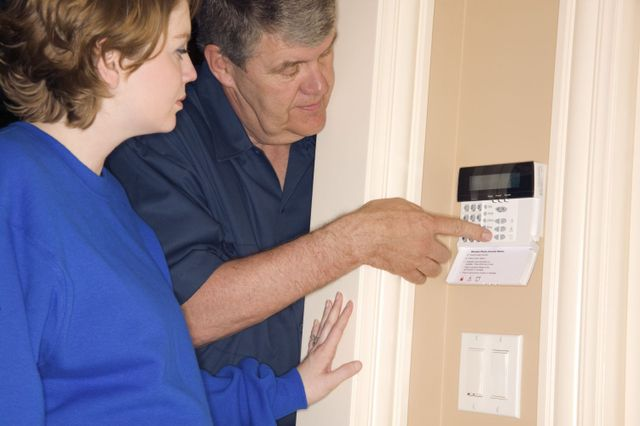 Man installing an alarm system and fire extinguishers in Anchorage, AK