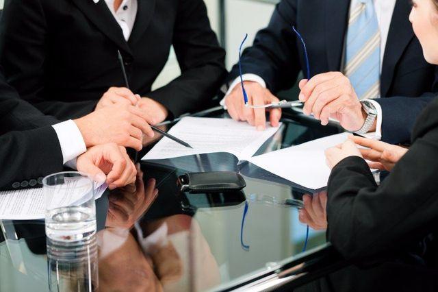 delle persone che discutono a un tavolo con dei documenti