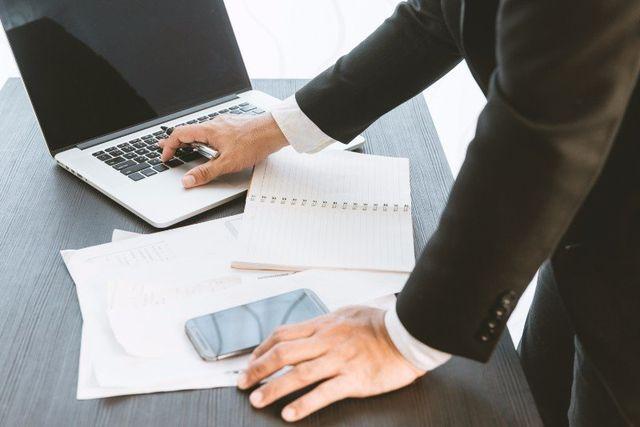 una mano appoggiata sulla scrivania e un'altra che usa un computer portatile