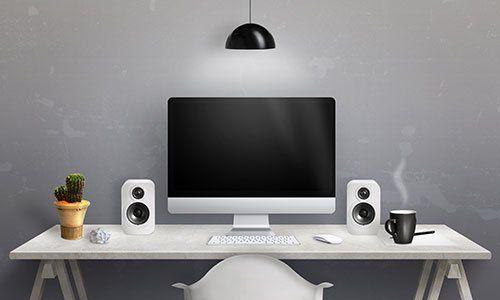 Una scrivania con un computer e due altoparlanti