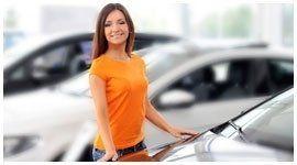 ragazza sorride appoggiata a un automobile