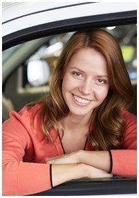 donna sorride  sporgendosi fuori dal finestrino di un auto