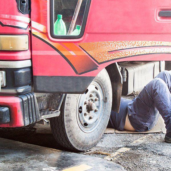 un meccanico sotto a un camion rosso