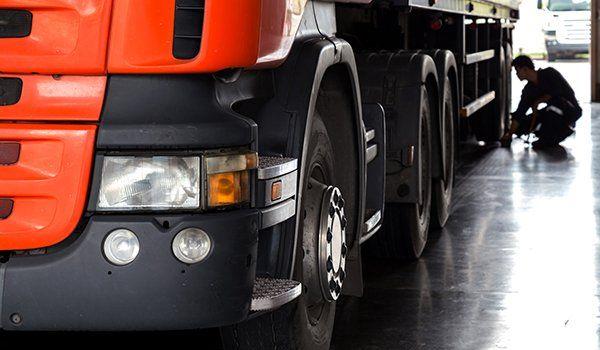 un camion rosso e nero e dietro un meccanico chinato a terra che controlla una ruota