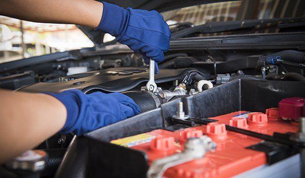 due mani con dei guanti blu e una chiave inglese in mano che sta avvitando un bullone di un motore