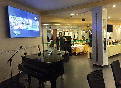 interno di un ristorante con vista di un pianoforte e di una tv a muro