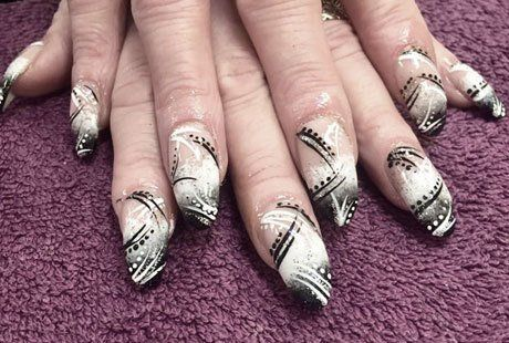 Nail extensions patterned in black and white dots and stripes