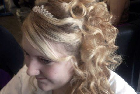 A blonde curly half-up, half-down style, with a diamante clip on the crown