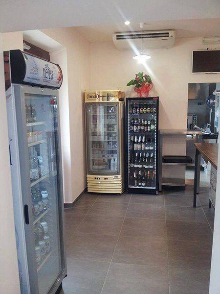 Interno del locale con tre frigoriferi per bevande e dolci