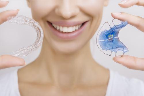 Donna che regge supporti e dentiere per l'ortodonzia