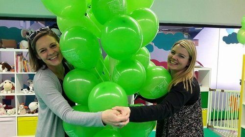 Due ragazze che si tengono per mano e in mezzo a loro dei palloncini verdi