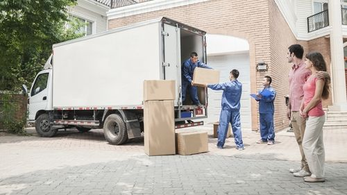 Group of movers putting boxes in a truck