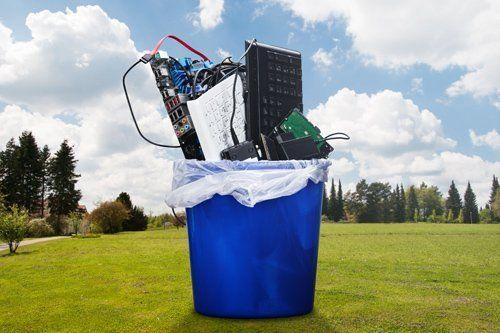 rifiuti elettronici in una pattumiera blu su un prato verde