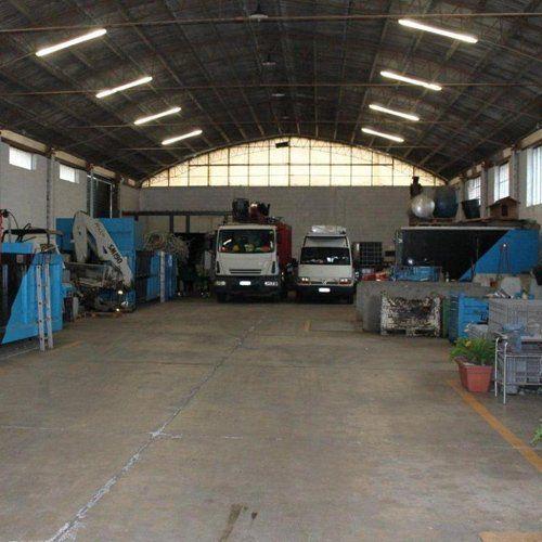 interno di uno stabile con camion e gru oltre a materiali di rottamazione