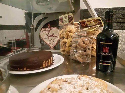 delle confezioni di biscotti, una torta al cioccolato e una bottiglia