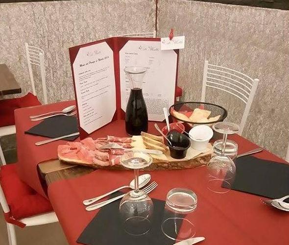 tavola apparecchiata con vino e antipasti misti