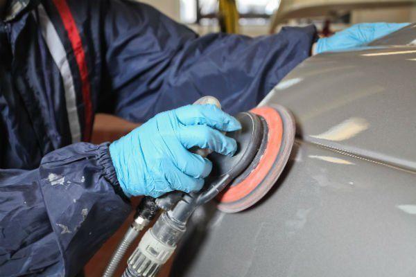 una mano con un guanto al lavoro con una lucidatrice sulla carrozzeria di una macchina