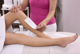 Therapist in a pink top, carrying out a waxing treatment on a lady's shins