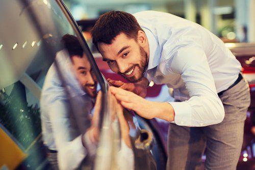 uomo che tocca la carrozzeria di una macchina