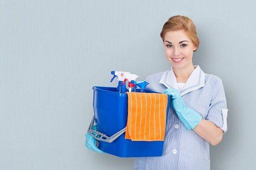 una donna con un secchio e dei prodotti di pulizia in mano