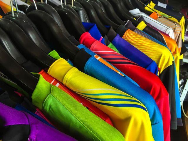delle magliette colorate su degli appendini