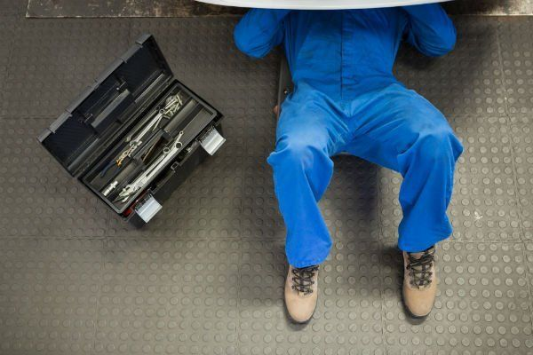 una cassetta degli attrezzi e un meccanico sdraiato che controlla il sotto di una macchina