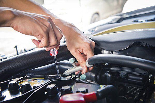 due mani con un cacciavite che riparano un motore