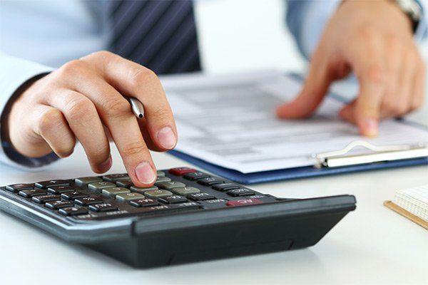 le mani di un uomo alla scrivania che esegue calcoli con una calcolatrice scorrendo il dito su di un documento