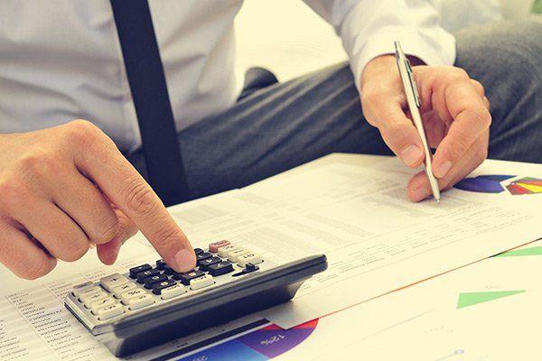 un uomo seduto utilizza una calcolatrice e scrive su dei fogli con grafici