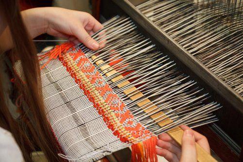 mani che intrecciano un tessuto sul telaio