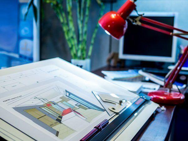 scrivania di progettista con computer e attrezzature