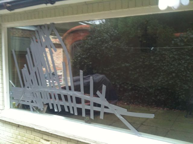 A glass window with safety tape on it