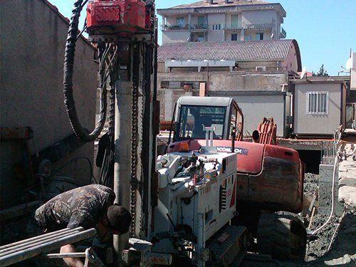 operaio mentre lavora in un cantiere con scavatrice e movimento terra