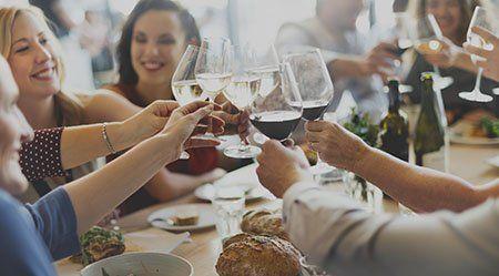 delle persone sedute a un tavolo che brindano con dei bicchieri