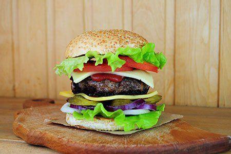 un tagliere con un hamburger con pane e verdure