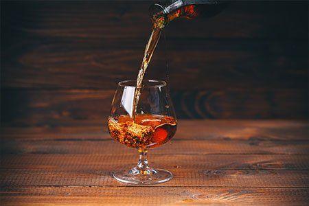 Versare brandy o cognac dalla bottiglia nel bicchiere su sfondo di legno