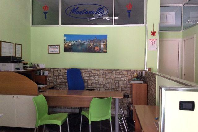 Vista interna di un ufficio, con sedie verdi, tavoli in legno ed altri arredi d'ufficio