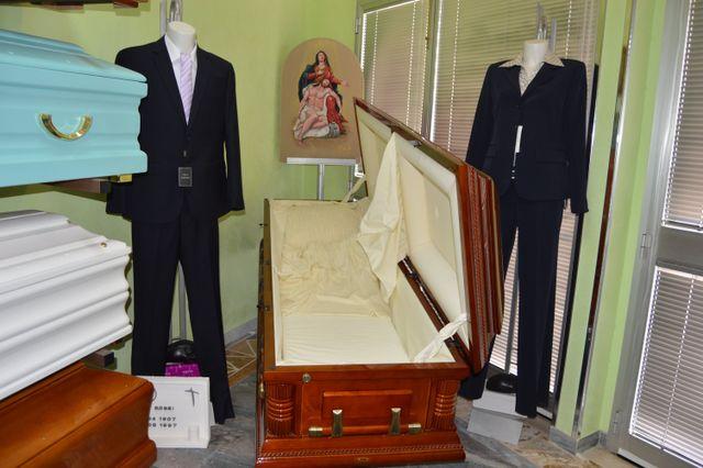 Assortimento di casse da morto in diversi colori e manichini con completi uomo/donna di colore nero
