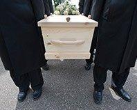 Sei uomini portando una bara in legno chiaro