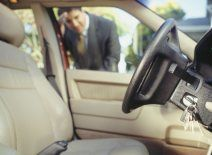 Businessman looking through window at keys locked in car — Locksmith in Estepona