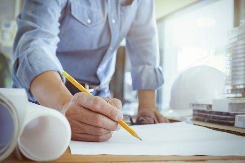una mano con una matita e un foglio davanti