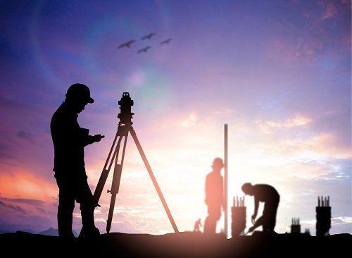 un uomo con un cavalletto per misurazioni elettroniche e altri uomini al lavoro