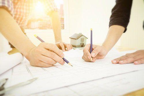 delle mani con delle matite e un progetto edile
