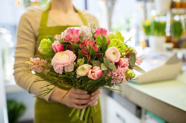 Una donna all'interno di un negozio di fiori con una maglia di color beige e un grembiule di color verde con un bouquet di fiori rosa e verdi